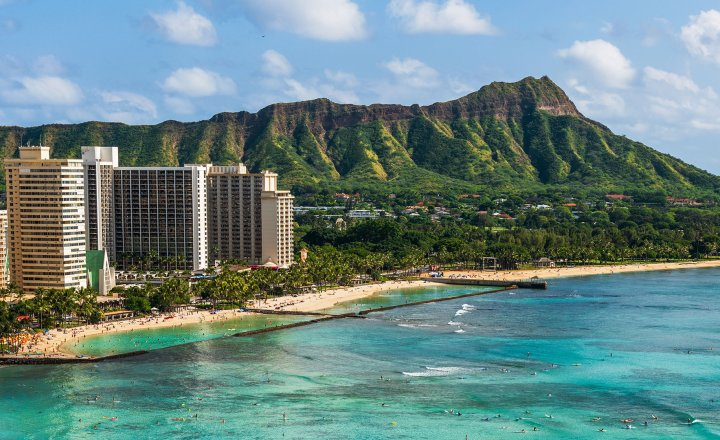 A beach and hotel in Honolulu with volcano background